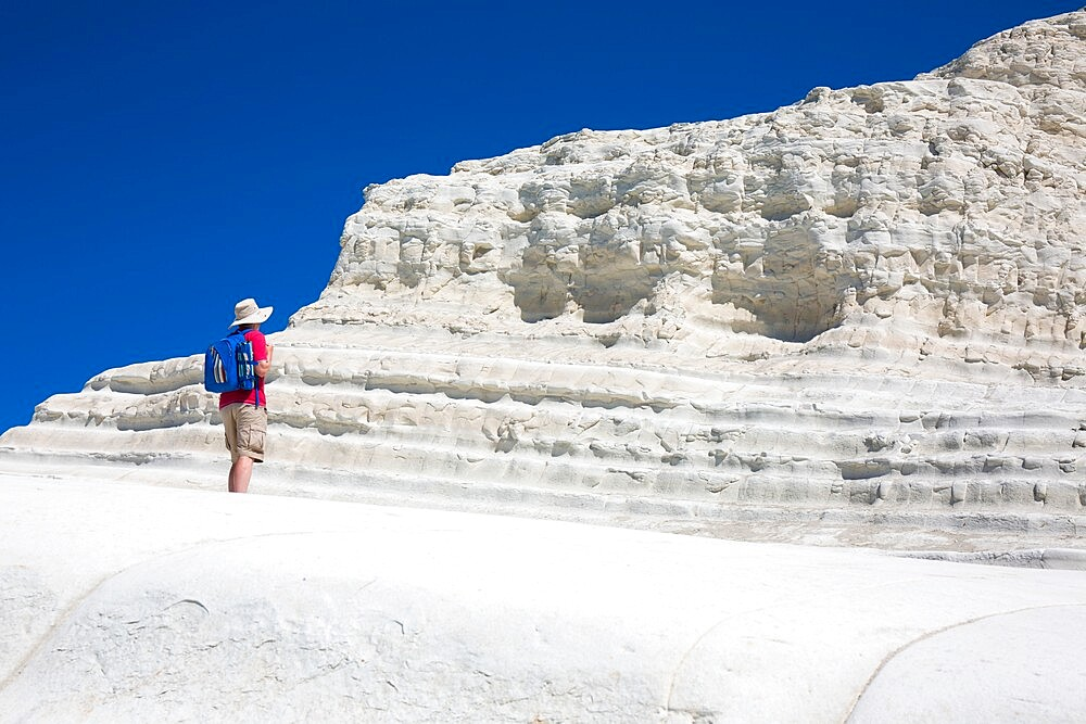 Visitor admiring the white limestone cliffs of the Scala dei Turchi, Realmonte, Porto Empedocle, Agrigento, Sicily, Italy