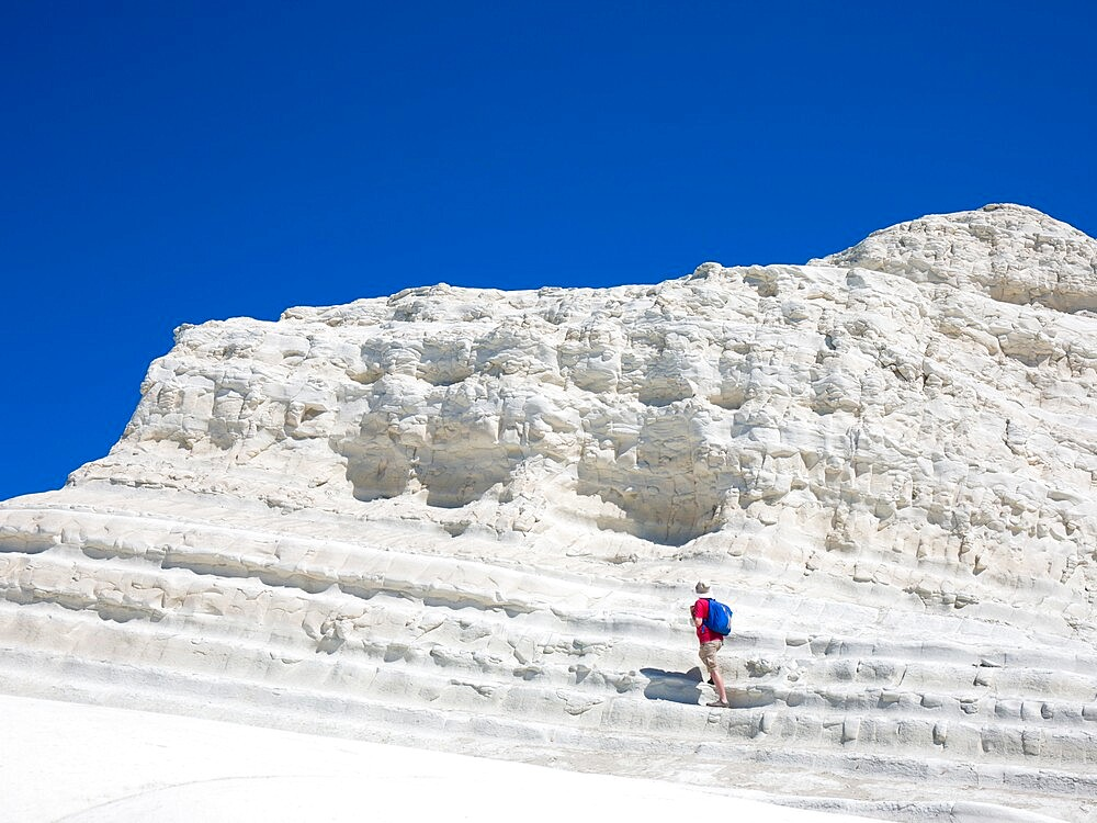Visitor ascending the white limestone cliffs of the Scala dei Turchi, Realmonte, Porto Empedocle, Agrigento, Sicily, Italy