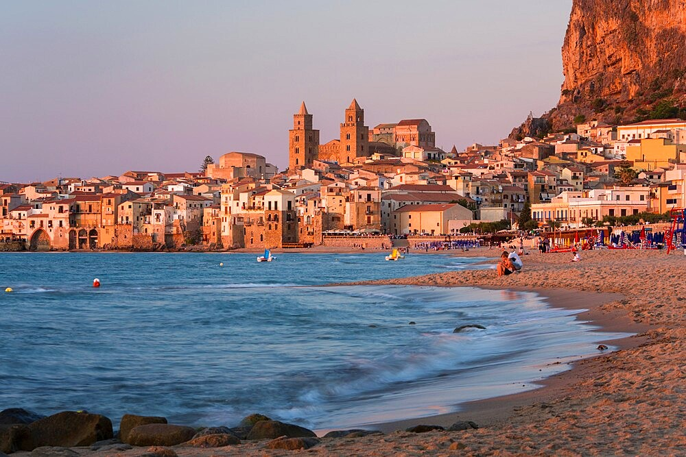 View from beach along water's edge to the town and UNESCO World Heritage Site listed Arab-Norman cathedral, sunset, Cefalu, Palermo, Sicily, Italy, Mediterranean, Europe