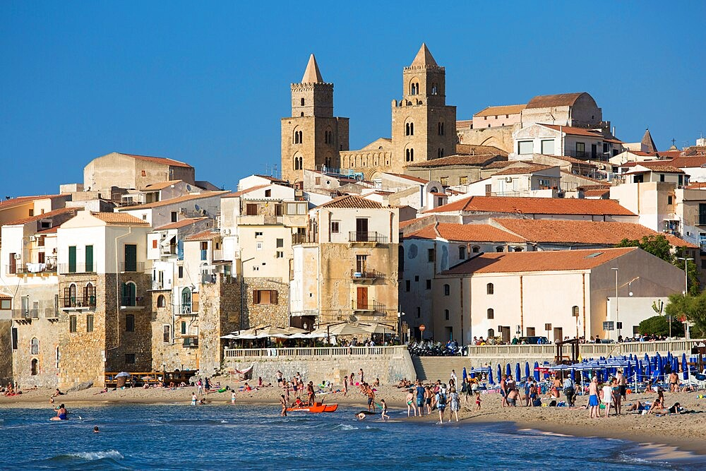 View from beach along water's edge to the town and UNESCO listed Arab-Norman cathedral, Cefalu, Palermo, Sicily, Italy - 1310-164