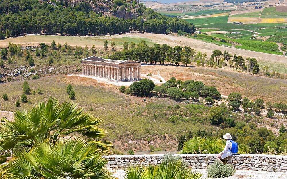 Visitor admiring view over the magnificent Doric temple at the ancient Greek city of Segesta, Calatafimi, Trapani, Sicily, Italy