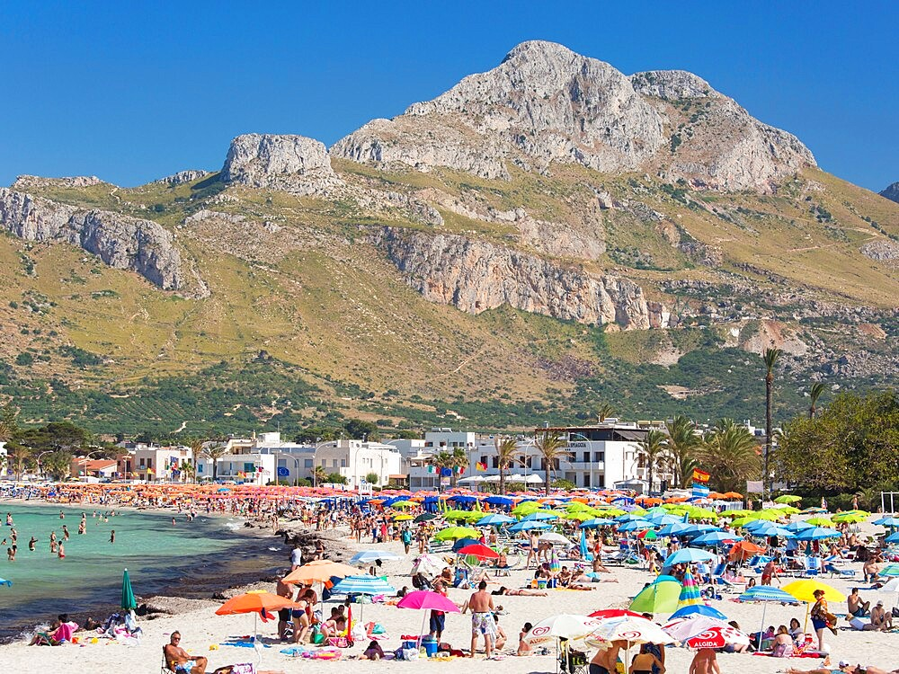 View across colourful crowded beach to the rugged slopes of Pizzo di Sella, San Vito Lo Capo, Trapani, Sicily, Italy - 1310-175