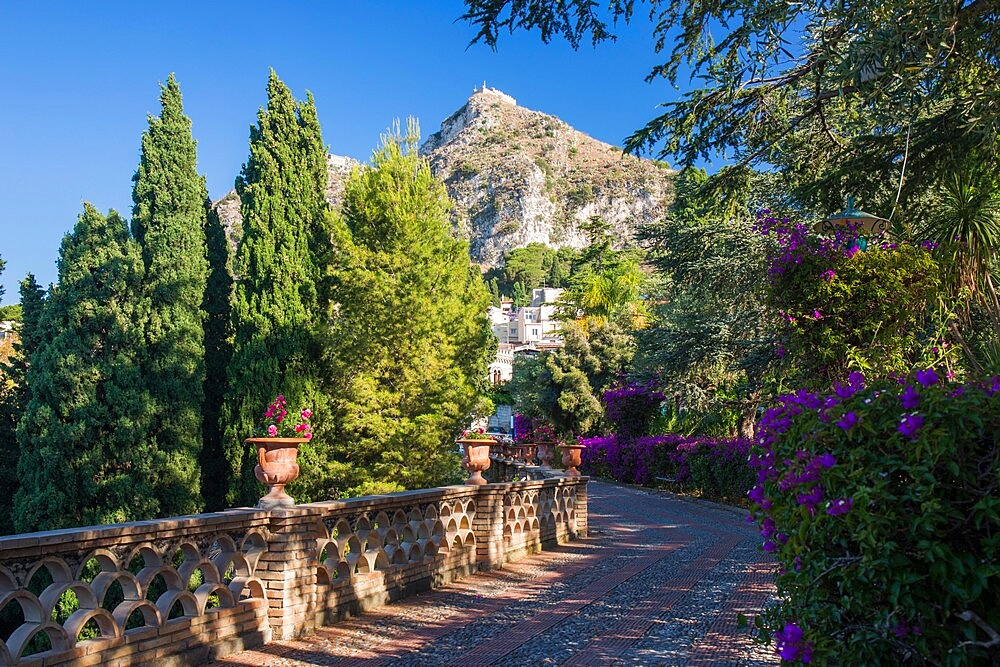 View along footpath in the gardens of the Villa Comunale, Saracen castle visible on hilltop, Taormina, Messina, Sicily, Italy - 1310-183