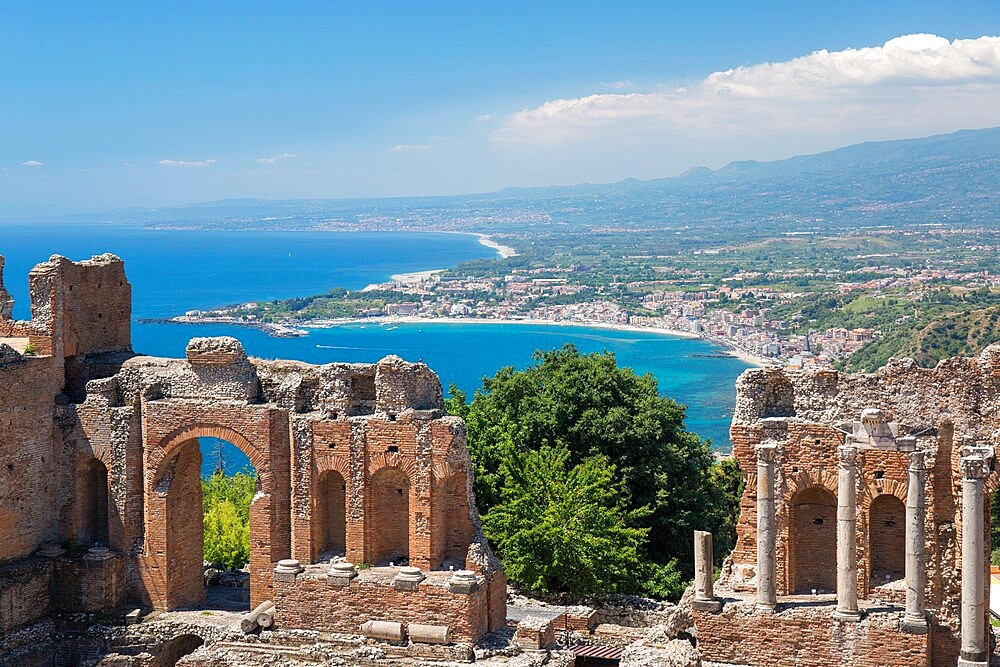 View from the Greek Theatre over the Bay of Naxos to distant Giardini-Naxos, Taormina, Messina, Sicily, Italy