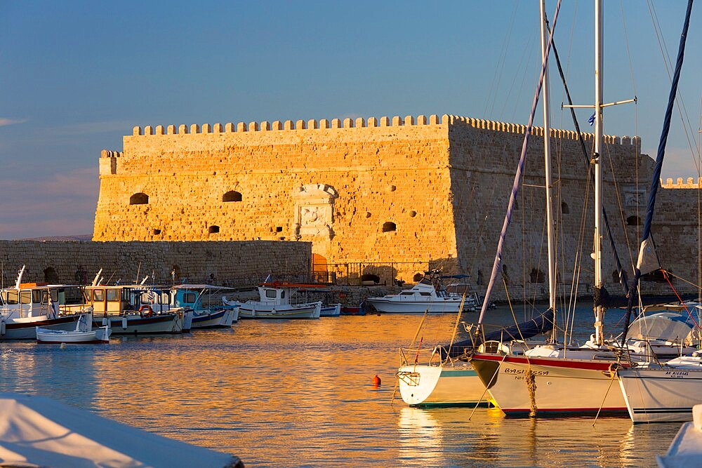 View across the Venetian Harbour, sunset, the Koules Fortress reflected in water, Iraklio (Heraklion), Crete, Greek Islands, Greece, Europe