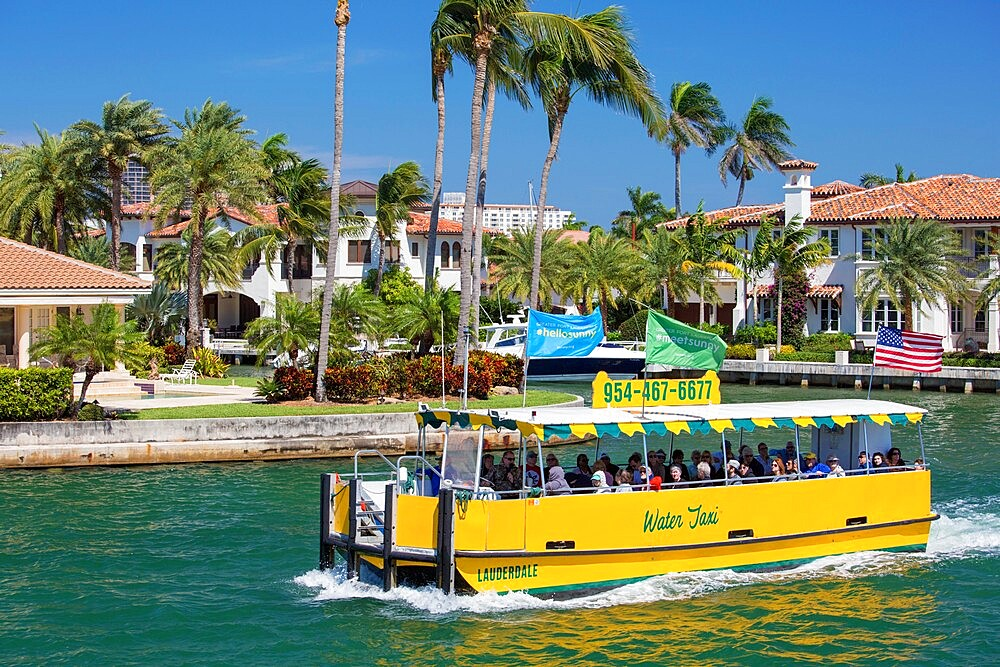 Colourful water taxi cruising along the New River, Las Olas Isles, Fort Lauderdale, Florida, USA - 1310-275