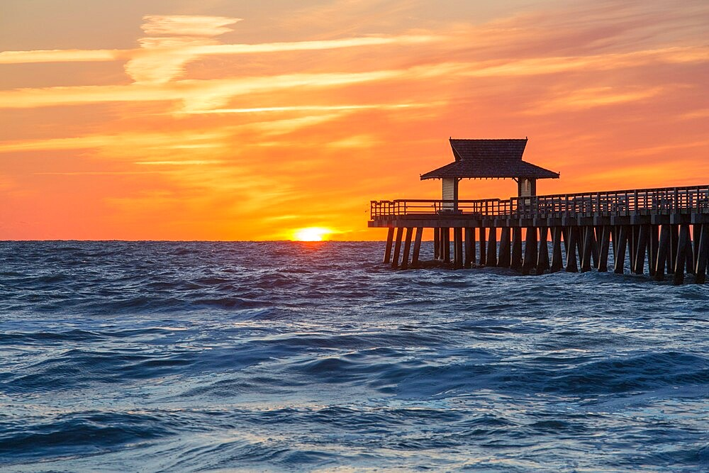 View across the Gulf of Mexico from beach beside Naples Pier, sunset, golden sky above horizon, Naples, Florida, USA - 1310-297
