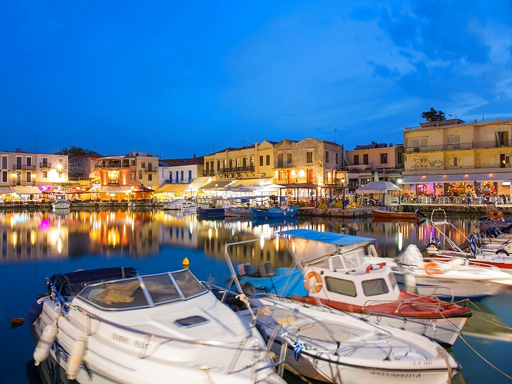 View across the Venetian Harbour at dusk, brightly lit restaurants reflected in water, Rethymno (Rethymnon), Crete, Greek Islands, Greece, Europe