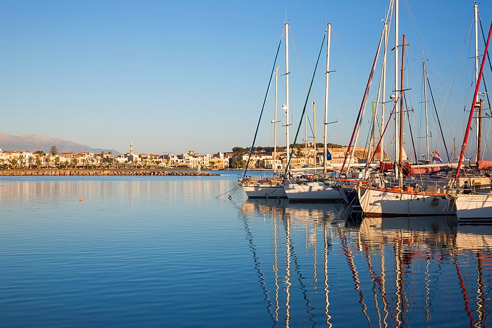 Yachts reflected in the still waters of the marina, early morning, Rethymno (Rethymnon), Crete, Greek Islands, Greece, Europe