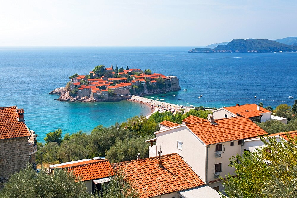 View over rooftops to Budva Bay and the exclusive island resort of Sveti Stefan, Budva, Montenegro, Europe