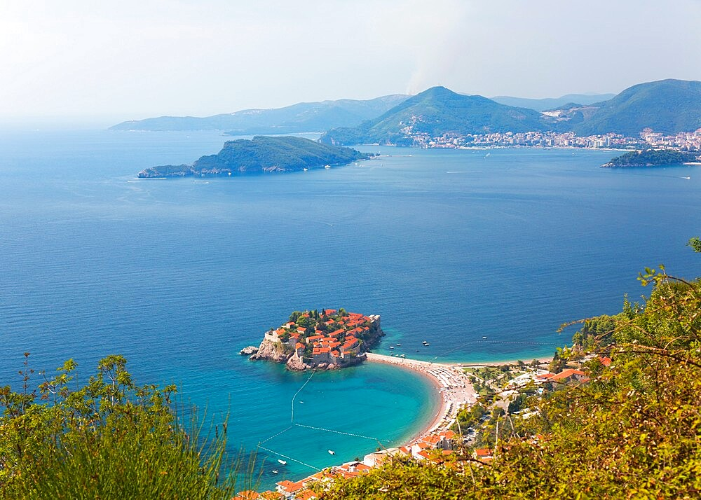 High angle view from hillside over Budva Bay and the exclusive island resort of Sveti Stefan, Budva, Montenegro, Europe