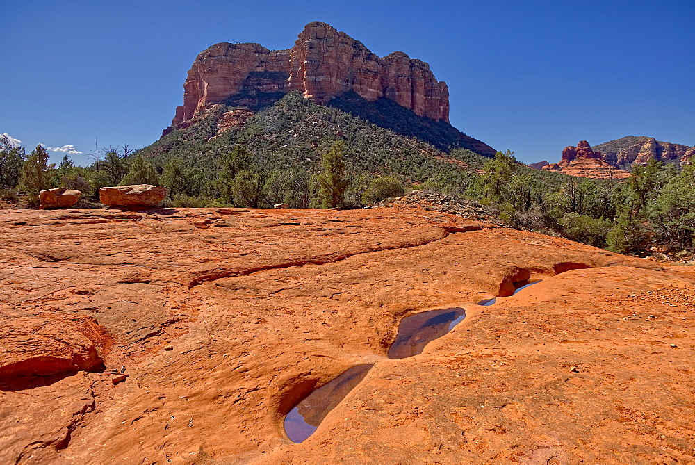 Reflections of Courthouse Butte in the Slick Rock Bowls along the Llama Trail in Sedona, Arizona, United States of America, North America