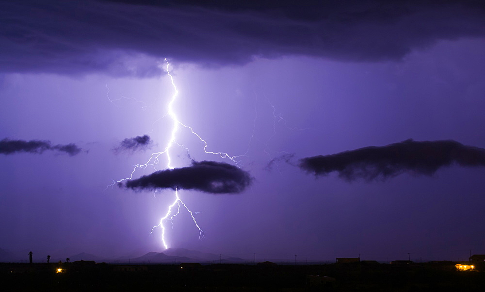 A bright lightning bolt passing through a cloud and striking in the Gila Bend Mountains south of Arlington Arizona.