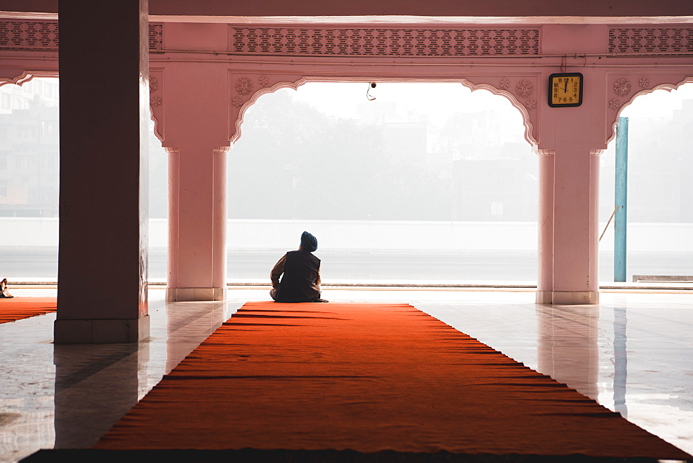 A man contemplates at Gurudwara Santokhsar Temple, Amritsar, Punjab, India, Asia
