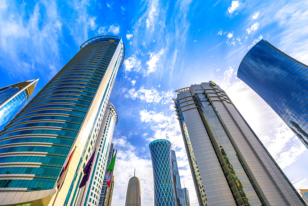 Low angle view of Al Fardan Towers complex and Doha Tower, iconic glassed high rises in West Bay, Doha, Qatar, Middle East
