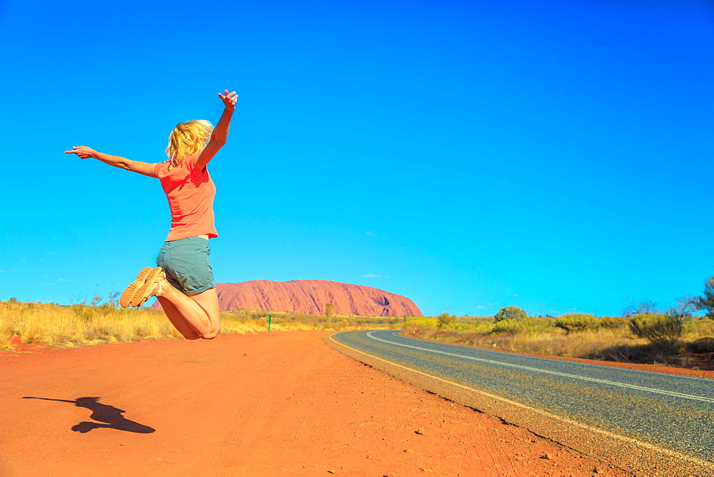 Tourist woman jumping at Uluru (Ayers Rock) in Uluru-Kata Tjuta National Park, UNESCO World Heritage Site, Northern Territory, Central Australia, Pacific