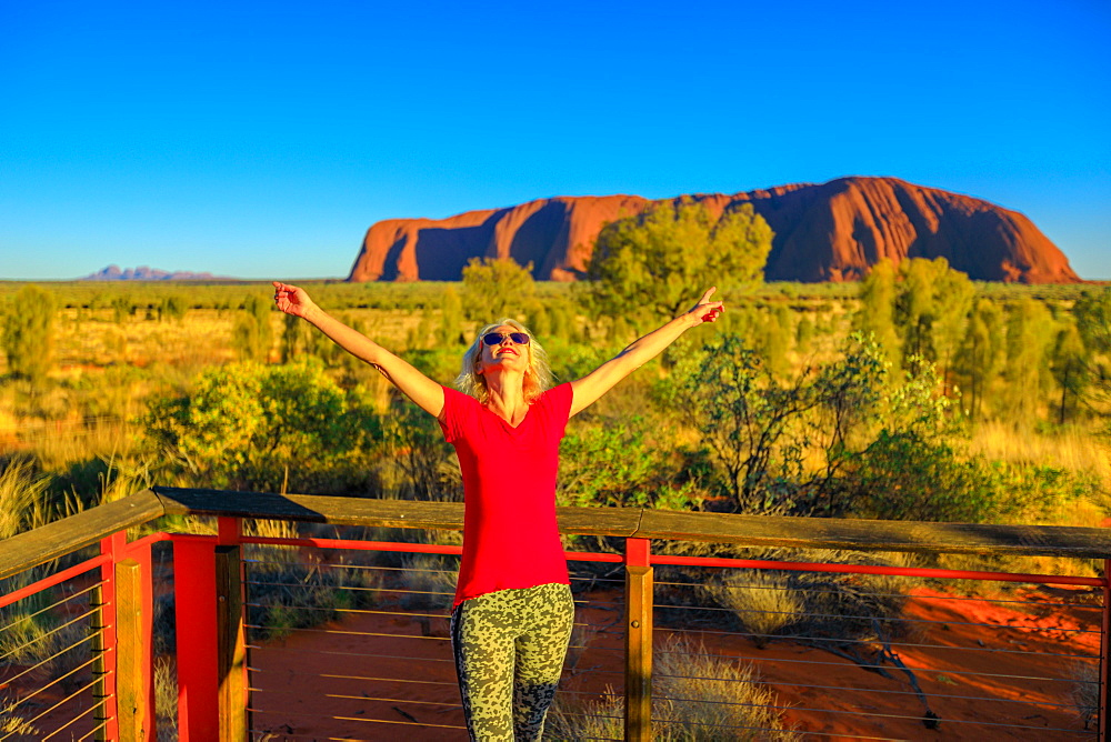 Tourist woman enjoying Uluru-Kata Tjuta National Park, UNESCO World Heritge Site, with Uluru and Kata Tjuta in the background, Northern Territory, Australia, Pacific