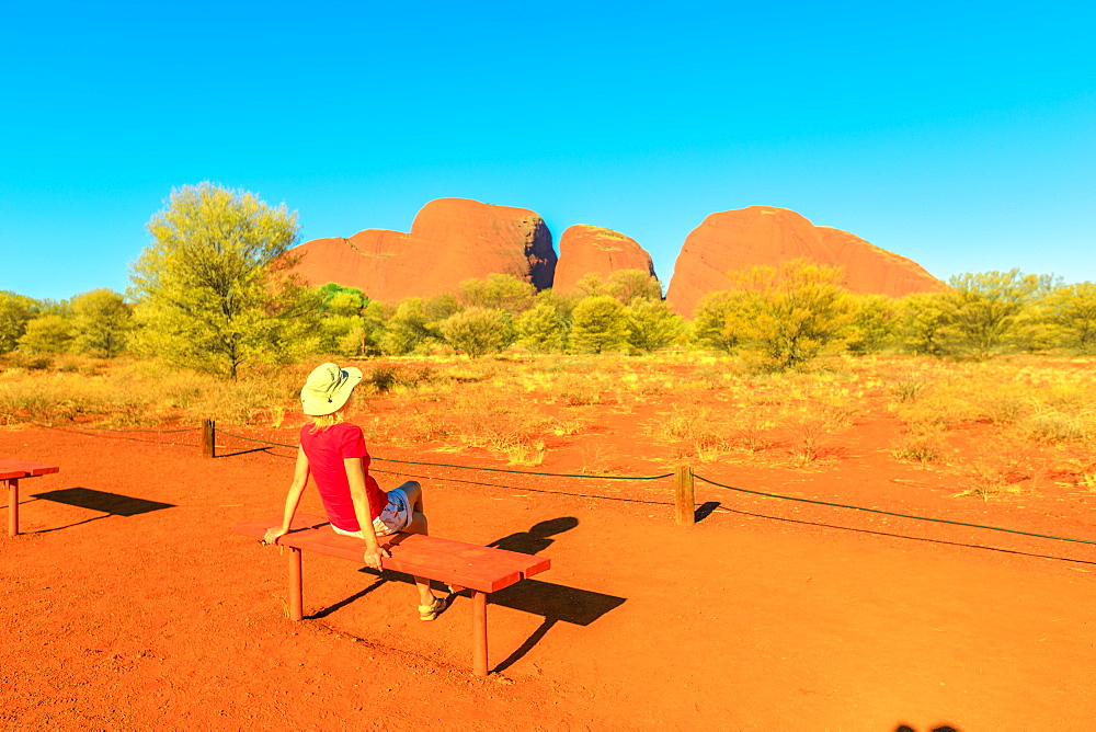 Tourist woman relaxing on a bench admiring the vibrant color of domed rock formations from Kata Tjuta Sunset viewing area, Uluru-Kata Tjuta National Park, UNESCO World Heritage Site, Northern Territory, Australia, Pacific