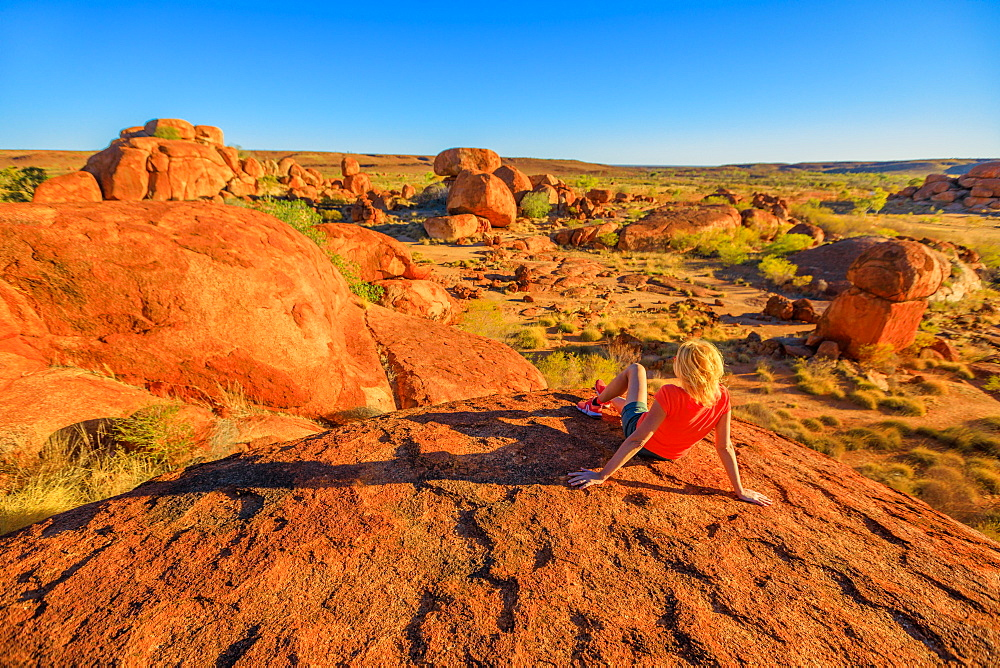 Tourist woman on the top view of Karlu Karlu (Devils Marbles) Conservation Reserve looking at panorama of granite boulders and rock formations at sunset, Outback, Northern Territory, Australia, Pacific - 1314-149