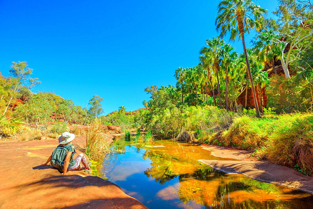 Tourist woman relaxing after trekking along Arankaia Walk in the heart of Palm Valley Oasis waterhole, Finke Gorge National Park. Tourism in Australian Outback, Northern Territory, Central Australia