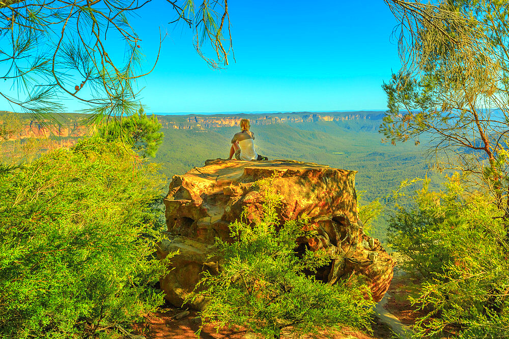 Tourist woman relaxing after hiking and enjoying panoramic views of granite boulders rock formations from Baltzer Lookout in Blue Mountains National Park near Sydney in New South Wales, Australia.