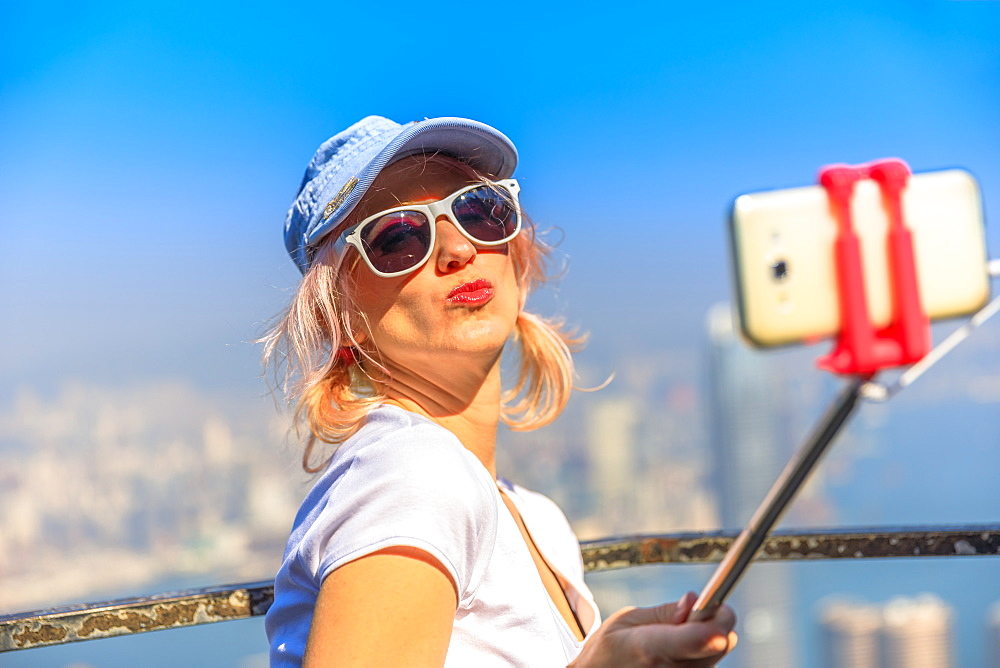 Tourist taking selfie stick picture with smart phone, enjoying view over Victoria Harbour from viewing platform on top of Peak Tower, Victoria Peak, Hong Kong, China, Asia