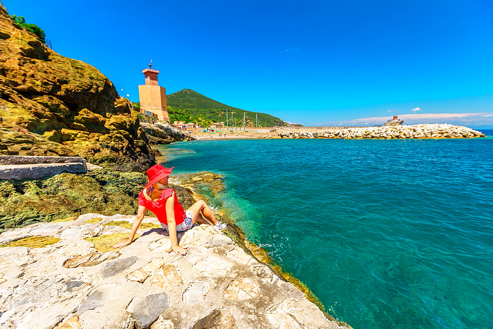 Happy woman resting over cliffs in Rio Marina beach on top with red hat. Caucasian tourist on holiday travel in Italy. Rio Marina town in summer on Elba island with clock tower on background.
