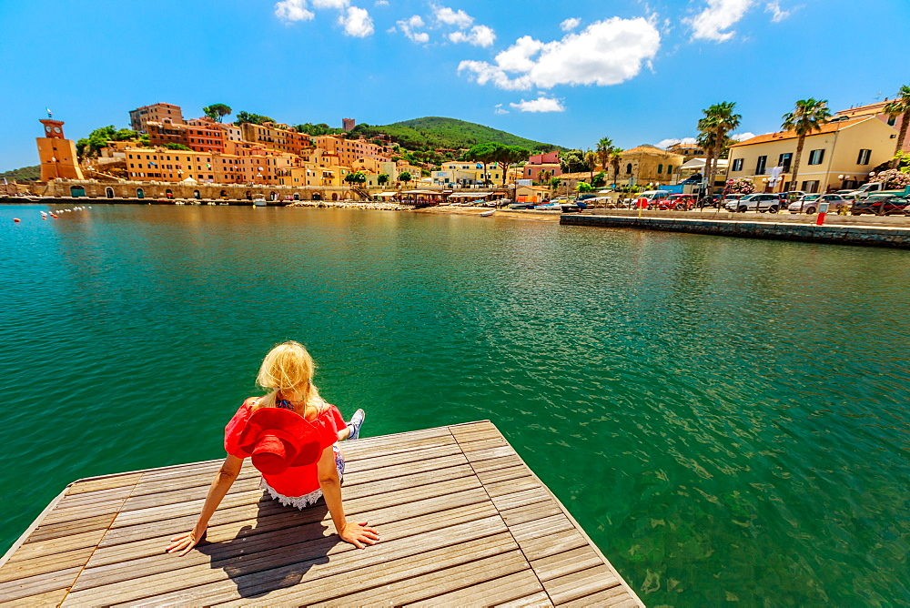 Blonde woman resting and sunbathing over jetty in Rio Marina harbor of Elba island in red suit. Lifestyle tourist girl on holiday travel in Italy, Europe. Rio Marina skyline cityscape on background.