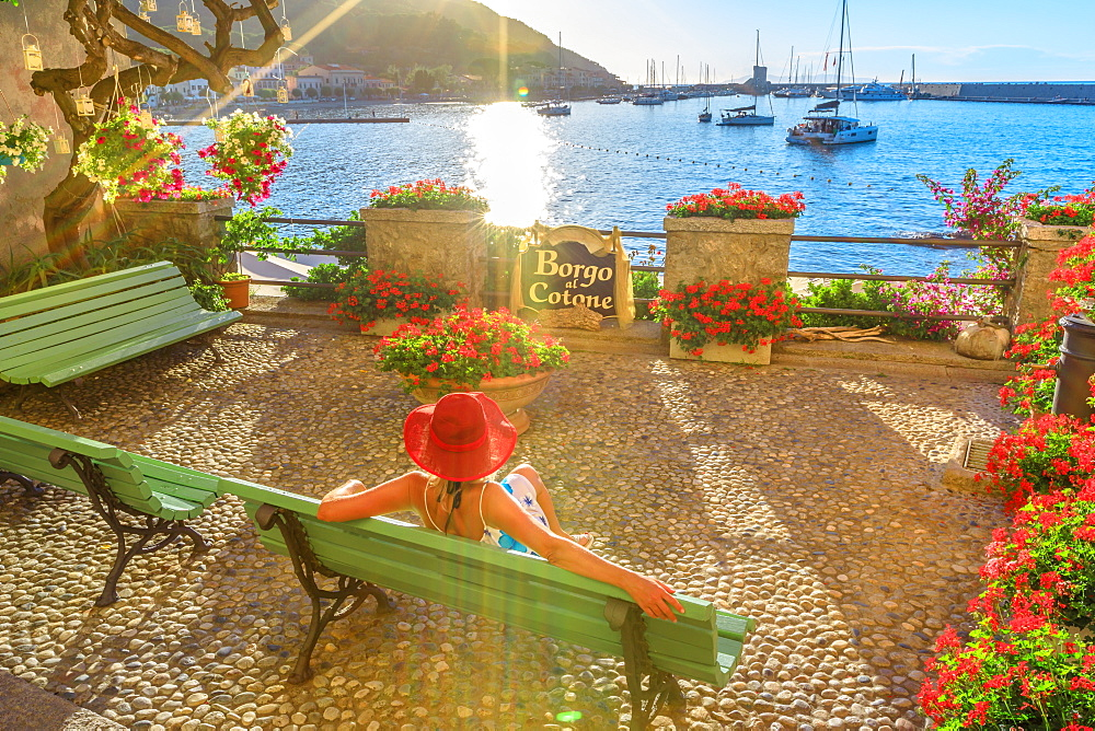 Elegant woman in red with hat at Marciana Marina waterfront, the flowery old district called Borgo al Cotone. Caucasian tourist on holiday travel in Italy. Marciana Marina in summertime on Elba island - 1314-222
