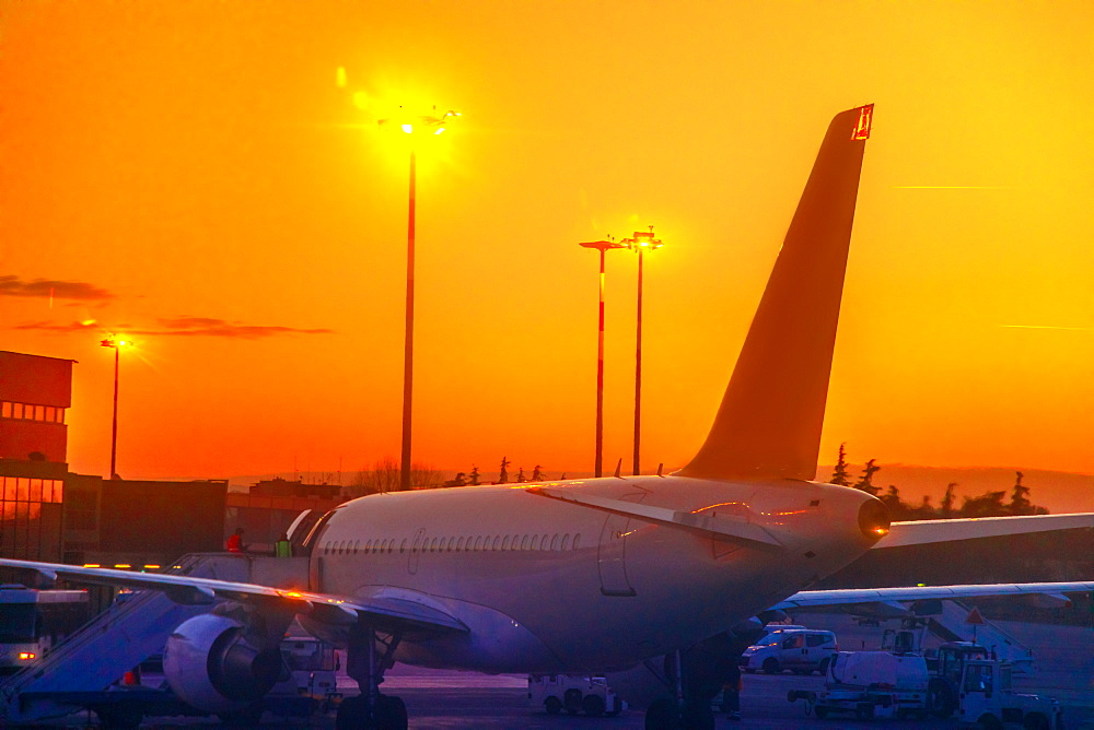 Commercial airplane parked in airport park at sunset, refuelling in taxi mode, United States of America, North America