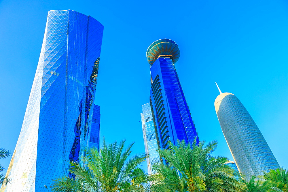 Low angle view of Al Fardan Towers complex and Doha Tower, iconic glassed high rises in West Bay, skyscrapers of Financial District in sunset light in 2019, Doha, Qatar, Middle East