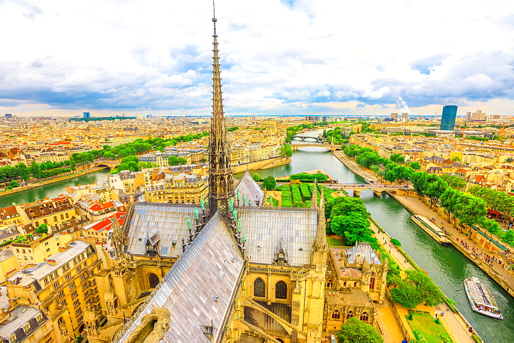 Detail of the spire of Notre Dame Cathedral (Our Lady of Paris) with statues, and city skyline, Paris, France, Europe