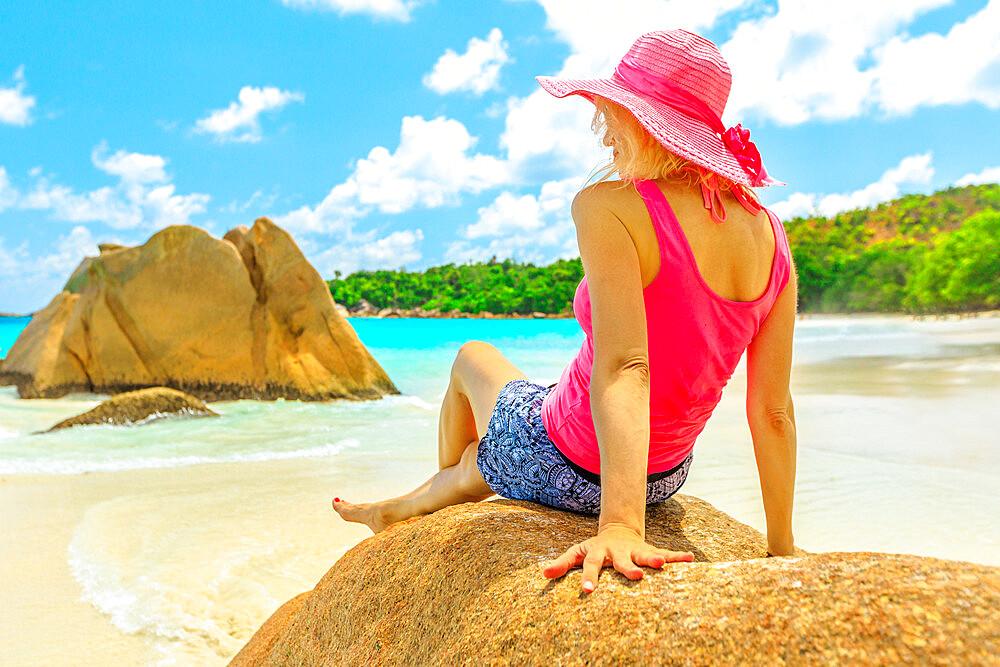 Caucasian blonde female sunbathes on a large granite boulder in popular Anse Lazio beach. Carefree woman looks turquoise waters of Indian ocean on Praslin Island, Seychelles. Sunny blue sky.