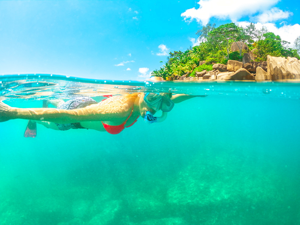 Split view of female tourist snorkelling underwater and landscape of St. Pierre Island coral reef, Seychelles, Indian Ocean, Africa