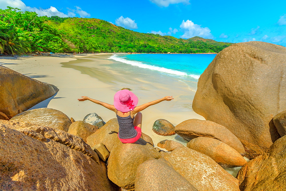 Aerial view and scenic landscape of bay of Anse Lazio. Tourist woman in pink hat sitting above a rock formations at Lazio beach. Female lifestyle looks turquoise Indian Ocean in Seychelles.