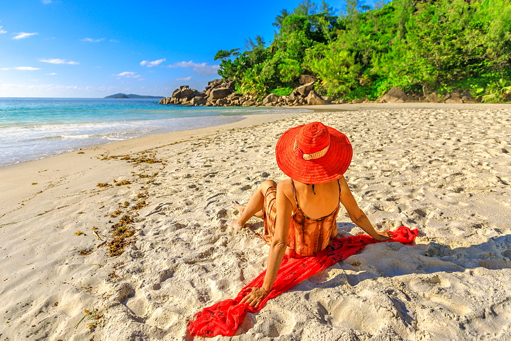 Elegant lifestyle female in red sunhat sitting on pristine white beach and looking horizon and turquoise sea at sunset light. Anse Georgette Beach, Indian ocean, Praslin Island, Seychelles.