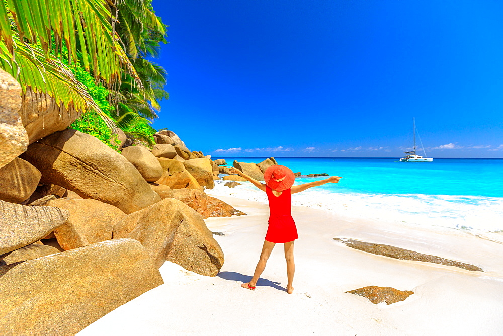 Tourist woman in red dress looking at turquoise sea and sailing boat and catamarans on horizon, Praslin Island, Seychelles, Indian Ocean, Africa