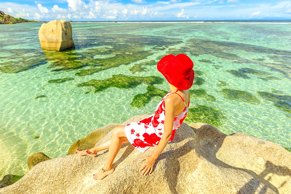 Tourist woman in red hat on a granite boulder at Anse Source d'Argent. Elegant female looks turquoise sea of Indian ocean on La Digue Island, Seychelles.Aerial view of tropical beach, scenic landscape