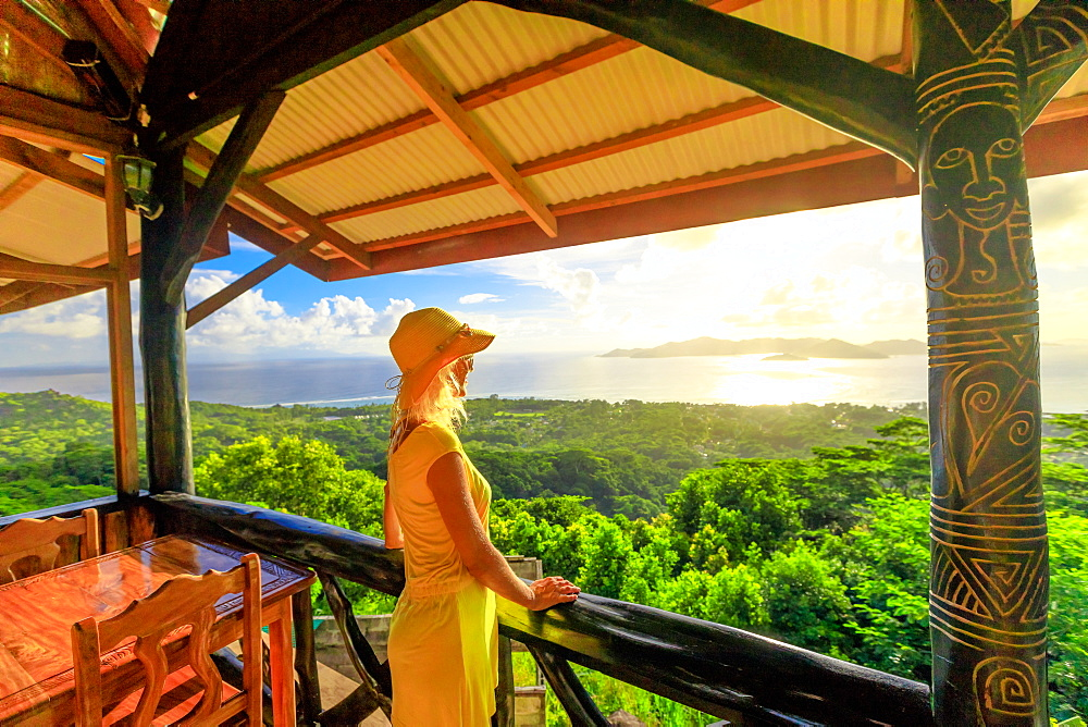 La Digue panorama from highest point of island at sunset. Lifestyle female enjoying spectacular views of the Seychelles and Indian Ocean.Elegant tourist woman in yellow dress looking at Praslin Island