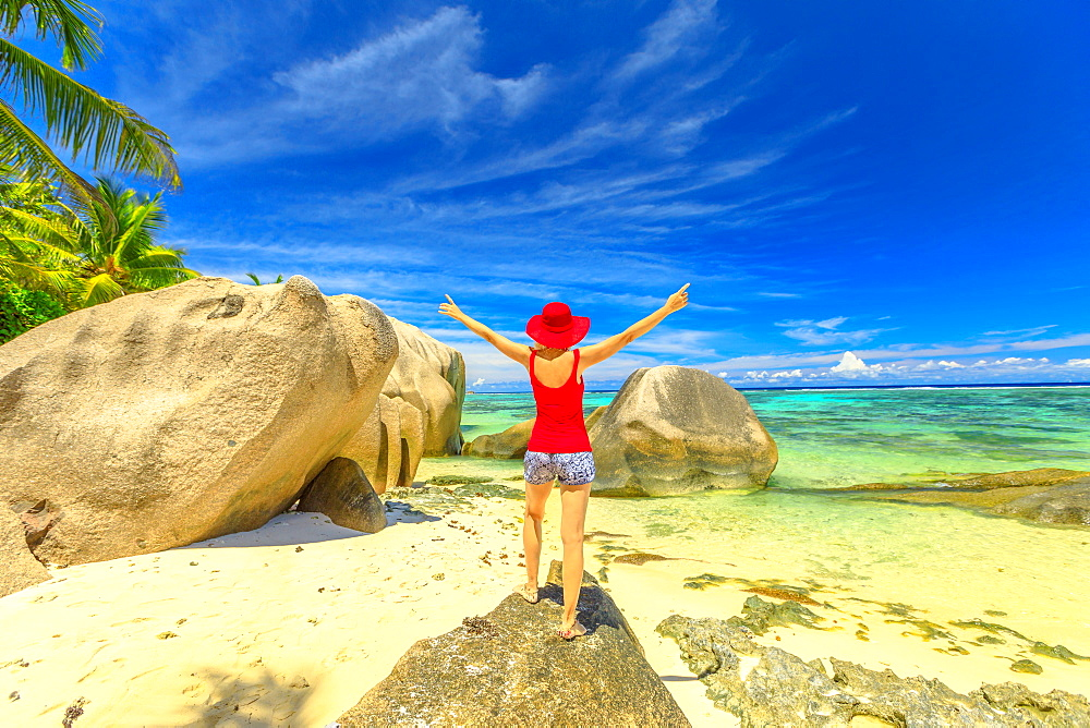 Tourist woman with raised arms in red hat standing on a boulder at Anse Source d'Argent. Young girl enjoying turquoise sea of La Digue, Seychelles. Scenic landscape of tropical beach.