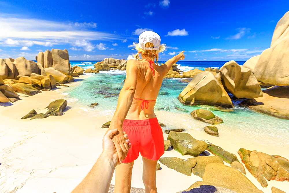 Blonde tourist woman in orange bikini holding hand of partner at Anse Marron of La Digue island of the Seychelles.