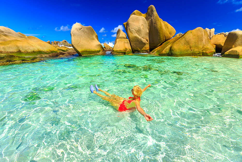 Swimming pool at Anse Marrone, La Digue. Happy woman in bikini lying on turquoise water in the natural pool of Seychelles beach