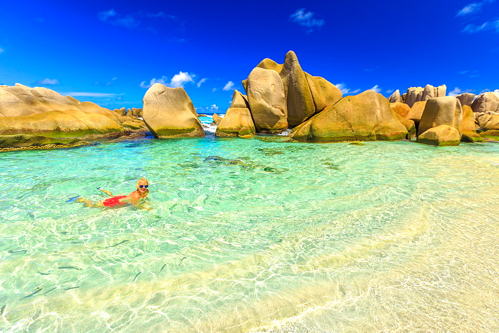 La Digue, Anse Marron, natural pool. Attractive woman in bikini, on crystal water of swimming pool at secret beach at Seychelles