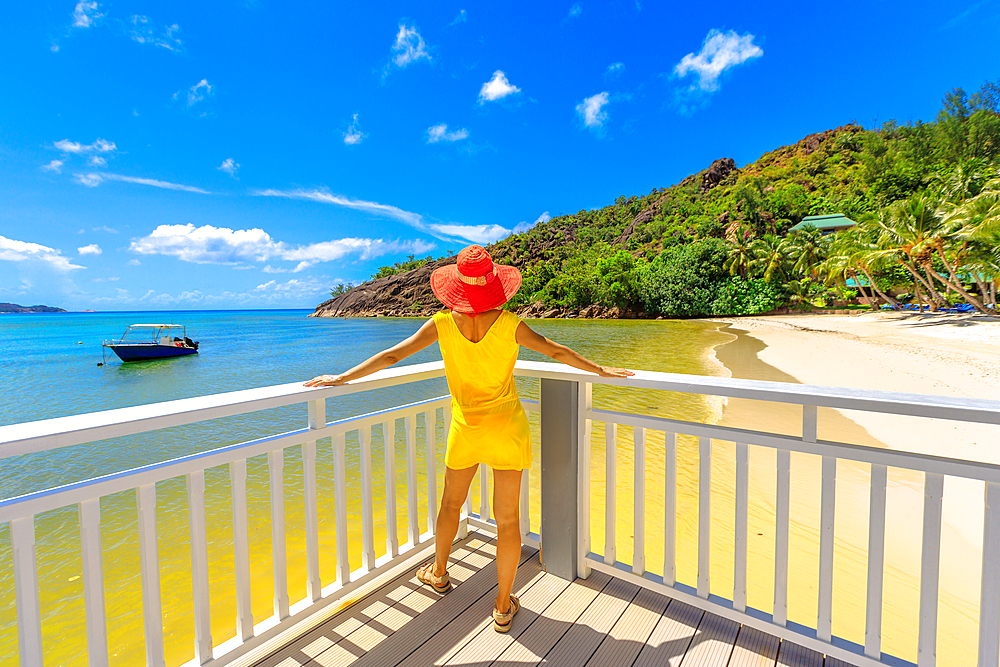 Woman in yellow dress on balcony of wooden jetty, looking at pristine white beach of Anse Gouvernement, near Cote d'Or Bay, in Praslin, Seychelles, Indian Ocean, Africa