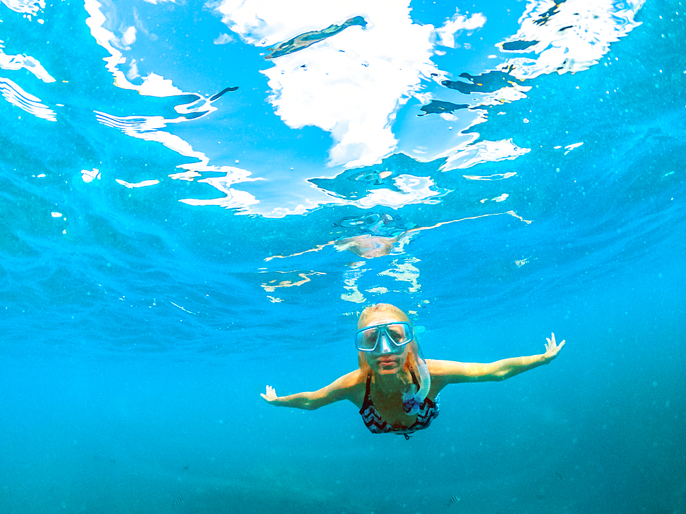 Female in bikini apnea at Seychelles, Indian Ocean. Travel lifestyle watersport activity. Young caucasian woman snorkeling in tropical turquoise sea. Woman free diving swims in coral reef.
