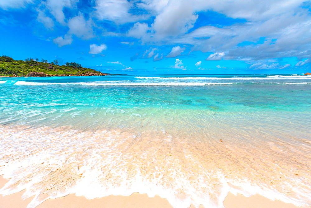 White sandy beach and turquoise clear sea of Anse Cocos can be reached with a trek starting from Grand Anse and passing through Petite Anse. Peaceful wallpaper of tropical Seychelles beach, La Digue.