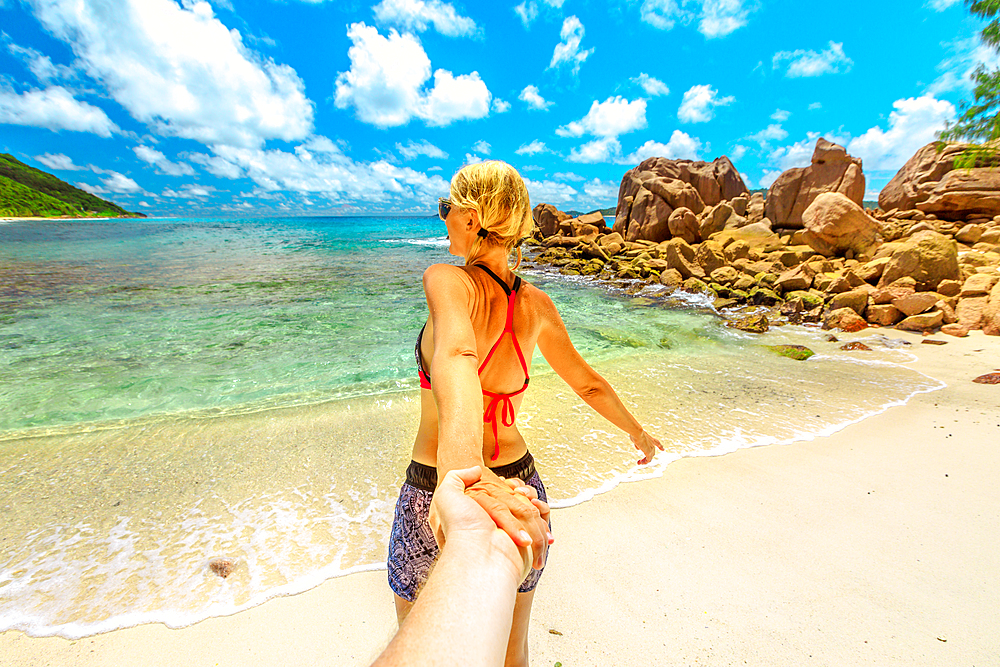 Follow me. Blonde tourist woman in bikini holding hand of partner at Anse Caiman Beach with natural pool in La Digue, Indian Ocean. Young girl enjoying at Seychelles.