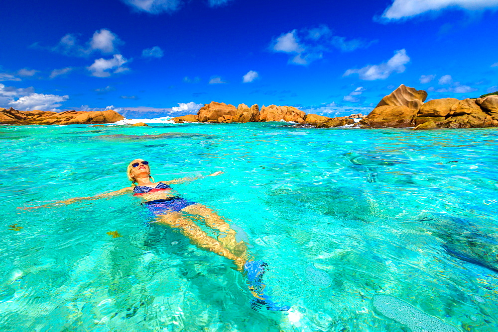 Swimming pool at Anse Cocos in La Digue. Happy woman in bikini lying on turquoise water of natural pool at Anse Cocos Beach protected by rock formations. Joyful girl at crystal lagoon at Seychelles.