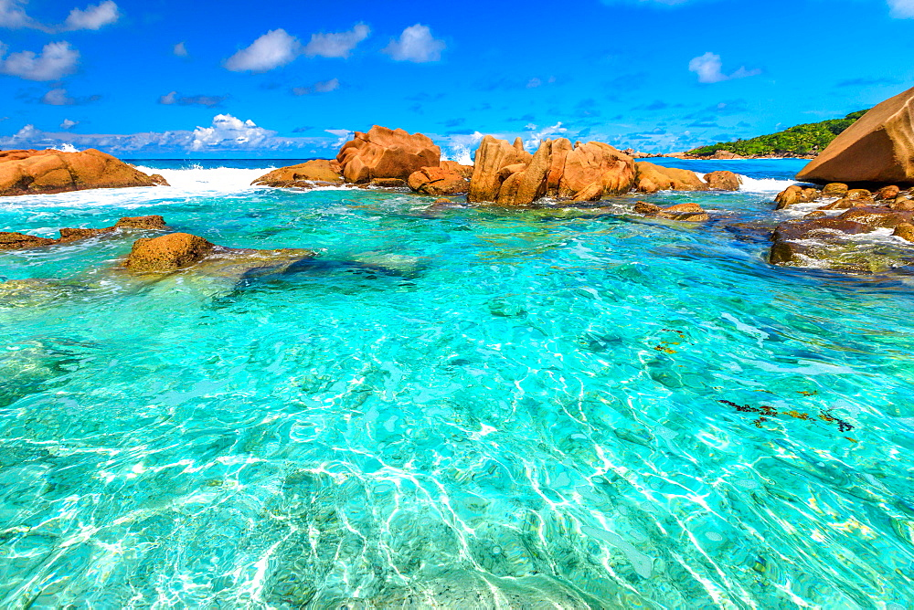 Turquoise sea of natural pool in La Digue. Clear calm waters of swimming pools at Anse Cocos near Grand Anse and Petite Anse protected by rock formations. Peaceful wallpaper of tropical Seychelles.