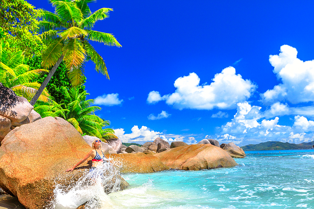 Funny tourist woman in splashing wave at Felicite Island, La Digue. Tropical jungle landscape of Seychelles. Granite boulder stone and waves crashing on shore. Leisure female in bikini at tropics.
